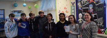 Picture of teacher and students with gift card.