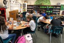 Student review over books to check out in their book tasting event.