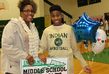 Basketball player and his mother accepting student of the month award at basketball game.