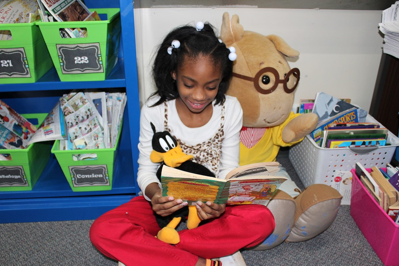 2nd grader reading to stuffed animal