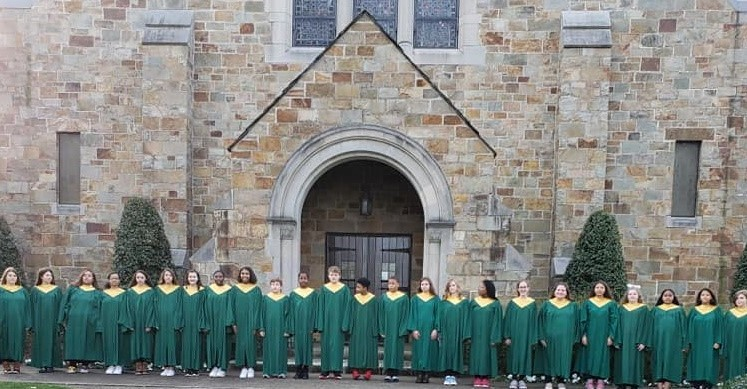 Students standing outside of church with choir robes on.