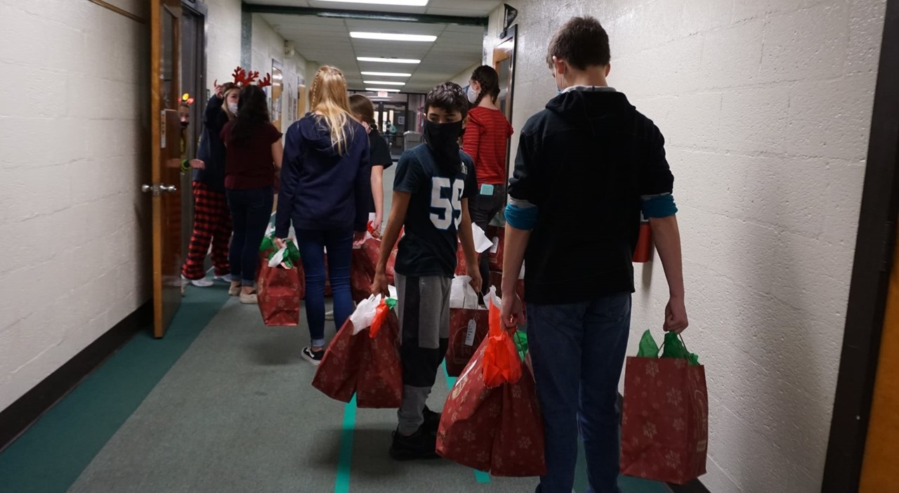 Students handing out gifts to students.