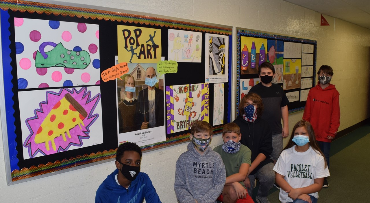 Students standing in front of their art work.