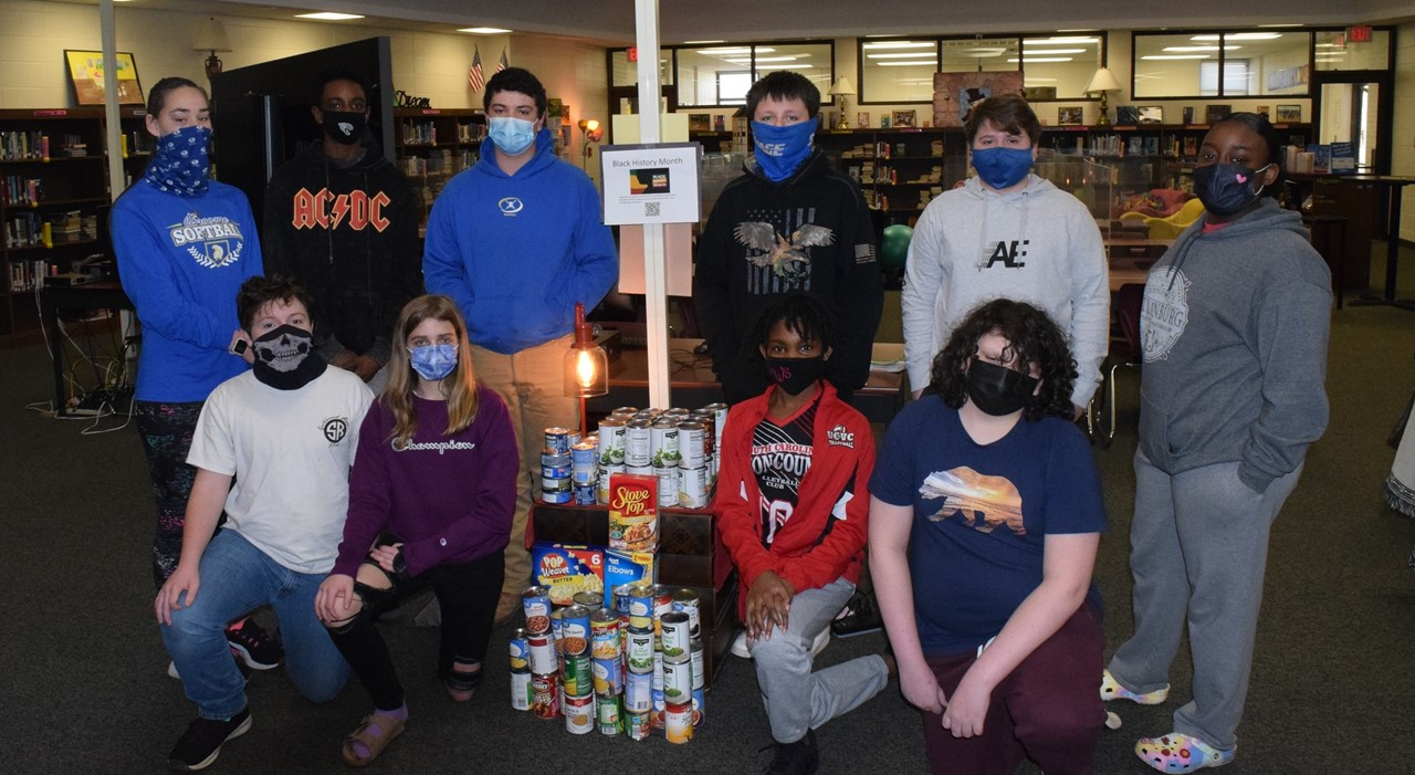 Students in front of cans.