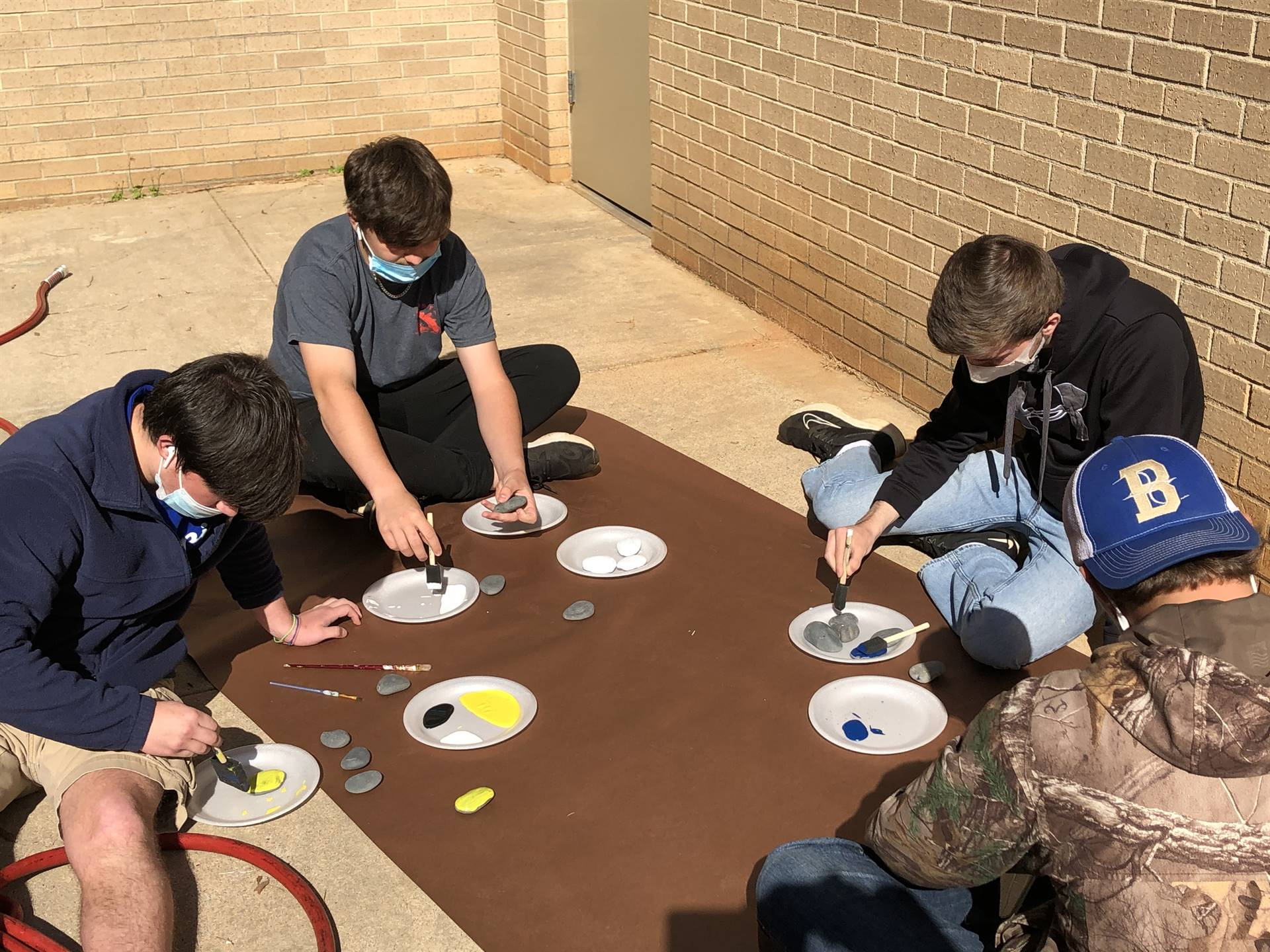 Group of Students Carefully Painting Rocks